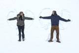 Loving couple making snow angel