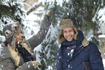 Happy couple enjoying snowfall