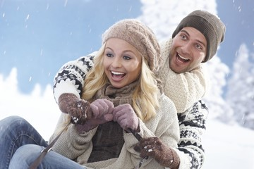 Young couple sledging