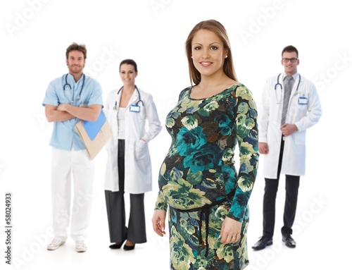 Pregnant woman with medical team in background