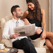 Young businessman relaxing with girlfriend while reading newspap
