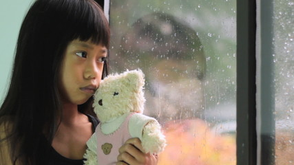 Asian Girl Comforted By Teddy Bear