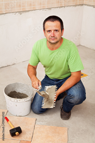 Worker laying ceramic floor tiles