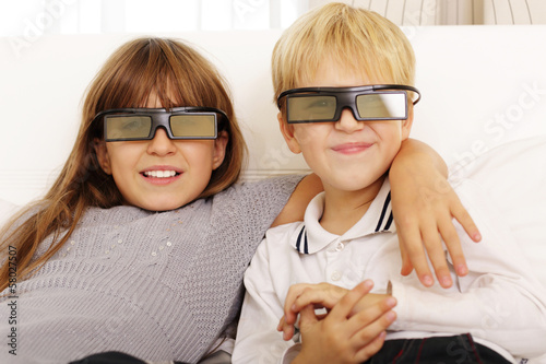 Brother and sister watching 3D movie at home