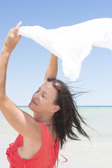 Woman with cloth in wind at tropical beach