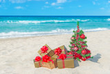 Fototapety Christmas tree and golden gift with big red bow on the sea beach