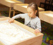 girl draws with sand on a light table