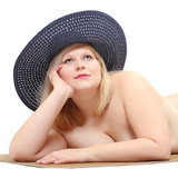 Overweight woman in straw hat sunbathing. Sun protection.