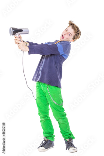 casual teenage boy is fighting with a hair dryer, isolated on wh