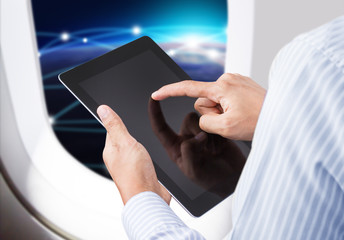 Businessman holding digital tablet in airplane with horizon