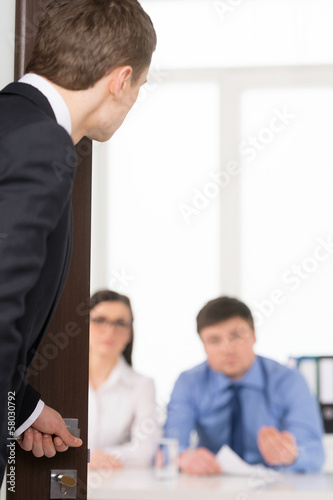 Worried man entering a room for job interview.