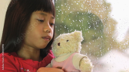 Sad Asian Girl Is Comforted By Teddy Bear