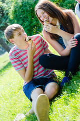 Happy teen couple eating ice cream on sunny summer day
