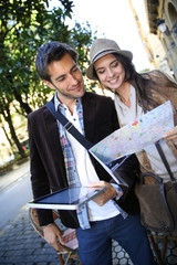 Couple of tourists walking in town with map and tablet
