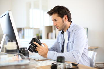 Photographer in office working on desktop computer