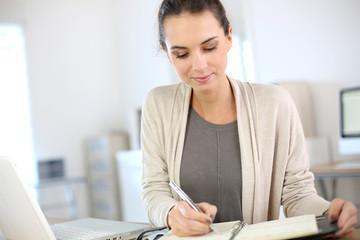 Businesswoman writing on agenda in office