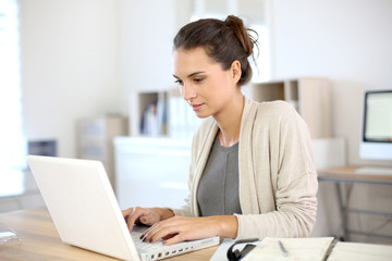Attractive woman working in office on laptop
