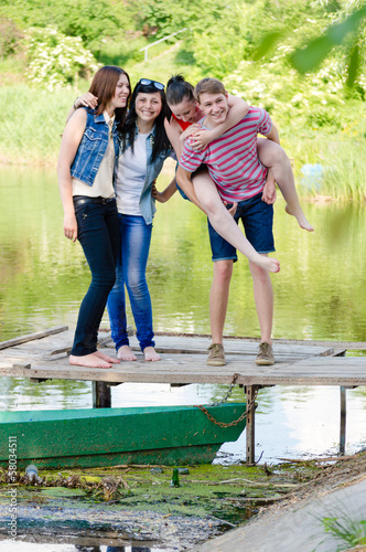 Four happy teen friends have fun on pier