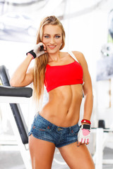 Confident athletic woman posing in gym