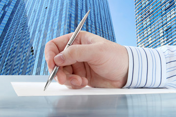Businessman's Hand with Pen on the Office Buildings Background