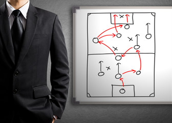 Businessman drawing tactic scheme on board