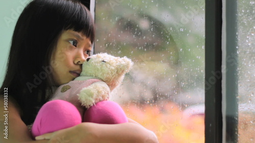 Sad Little Girl Sits By Window On Rainy Day