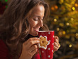 Smiling woman with christmas cookie and cup of hot chocolate
