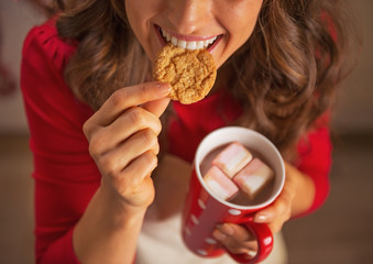 Closeup on happy housewife drinking chocolate and eating cookie