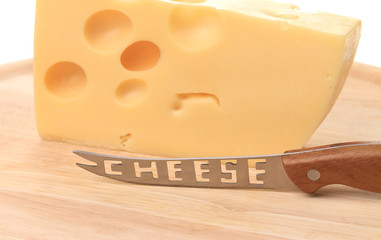 Delicious cheese and knife on wood