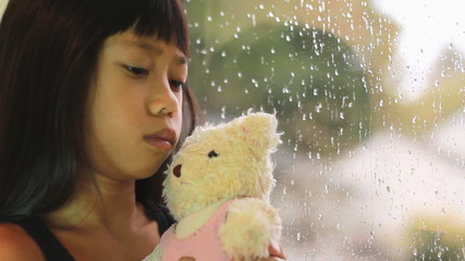 Sad Seven Year Old Asian Girl By Window