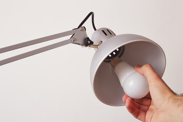 Hand changing a regular light bulb for LED