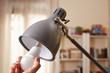 Leinwandbild Motiv Hand changing a regular light bulb for LED