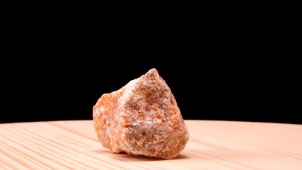 Orange calcite raw mineral stone revolves on the board