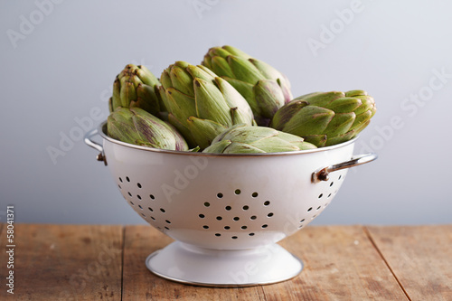 Raw pile of artichokes on colander
