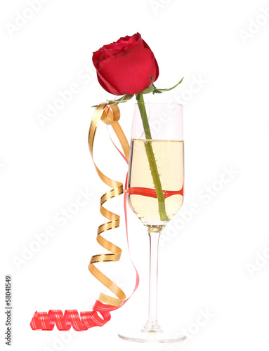 Red rose in glass of champagne.