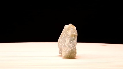 Aventurine green raw mineral stone revolves on the board