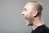 portrait of angry man screaming isolated on gray background with