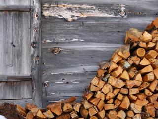 Brennholz an der Holzwand einer Almhütte