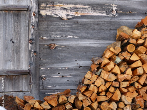 canvas print picture Brennholz an der Holzwand einer Almhütte
