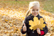 Girl with autumn leaf in hand
