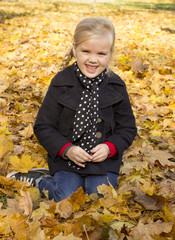 beautiful cheerful girl among autumn leaves