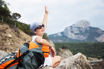 Young happy woman with backpack relaxing