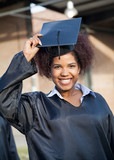 Student In Graduation Gown Wearing Mortar Board On Campus