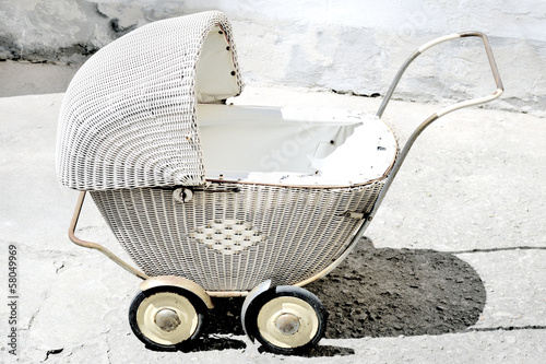 Picture shows antique, wicker stroller for children.