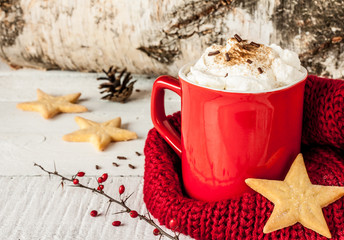 Winter whipped cream hot coffee in a red mug with cookies