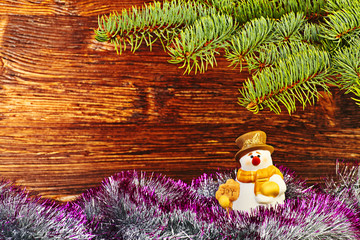 Christmas decoration. Snowman, tinsel and fir-tree. Selective fo