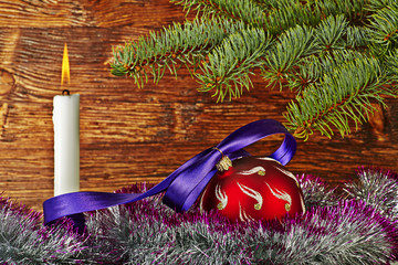 Christmas decoration. Red ball, violet ribbon, fir-tree, candle