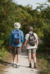 Mature couple holding hands and hiking on nature trail