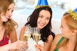 three women wearing hats with champagne glasses