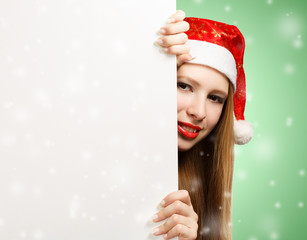 Young woman in santa claus hat with christmas card